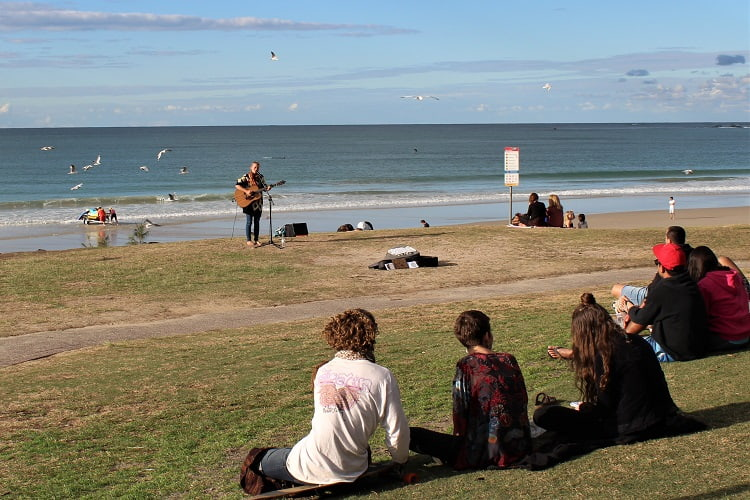 Watching a busker at Main Beach in Byron Bay.