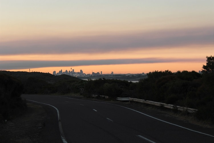 View of Sydney CBD skyline at sunset from Cape Solander Drive in Kurnell NSW.