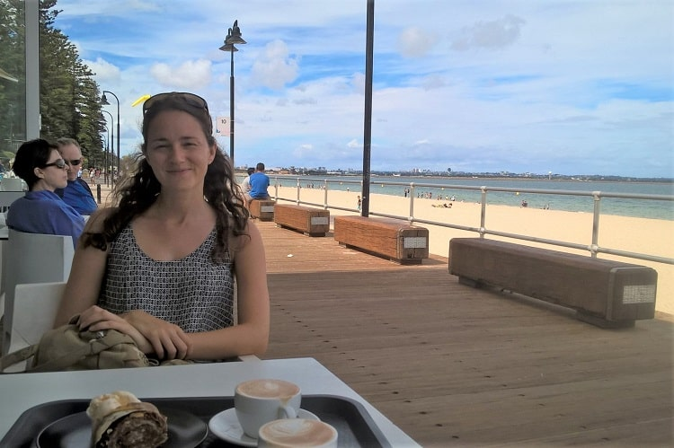 An expat enjoying coffee and cake at Brighton Le Sands beach café in Sydney.