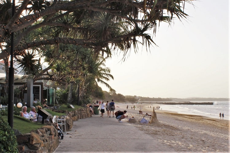 A beautiful sunset at Main Beach in Noosa Heads. Holidaymakers eating at beachfront restaurants on Hastings Street.