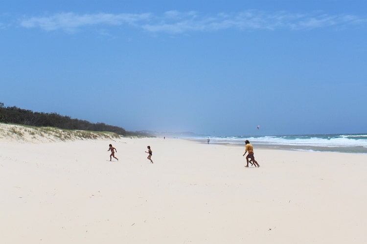A family running across the stunning white sand at Peregian Beach, Queensland.